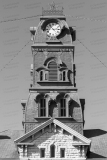 An image of the clock tower of the Hood County Courthouse in Granbury, Texas.  Designed by W.C. Dodson and built in 1890, the Granbury courthouse continues to host county offices, though most judicial functions have been relocated a few blocks to the west to the Hood County Justice Center, which was completed in 2006.  The limestone Hood County Courthouse, a Second Empire structure, is listed on the National Register of Historic Places and is a Texas Historic Landmark.  This image © Capitolshots Photography/TwoFiftyFour Photos, LLC, ALL RIGHTS RESERVED.