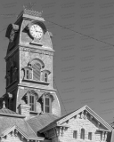 A photo of the clock tower of the Hood County Courthouse in Granbury, Texas.  Designed by W.C. Dodson and built in 1890, the Granbury courthouse continues to host county offices, though most judicial functions have been relocated a few blocks to the west to the Hood County Justice Center, which was completed in 2006.  The limestone Hood County Courthouse, a Second Empire structure, is listed on the National Register of Historic Places and is a Texas Historic Landmark.  This photo © Capitolshots Photography/TwoFiftyFour Photos, LLC, ALL RIGHTS RESERVED.
