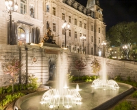 An image of the Quebec Parliament Building at night.  In the foreground is a fountain which includes two sculptures by Louis-Philippe Hebert: on top, A Halt In The Forest, and, below, The Nigog Fisherman, both of which honor the first residents of Quebec.  Designed by Eugene-Etienne Tache, the Quebec Parliament Building (Hotel du Parlement du Quebec), a Second Empire masterpiece, was built in Quebec City between 1877 and 1886.  This image © Capitolshots Photography/TwoFiftyFour Photos, LLC, ALL RIGHTS RESERVED.